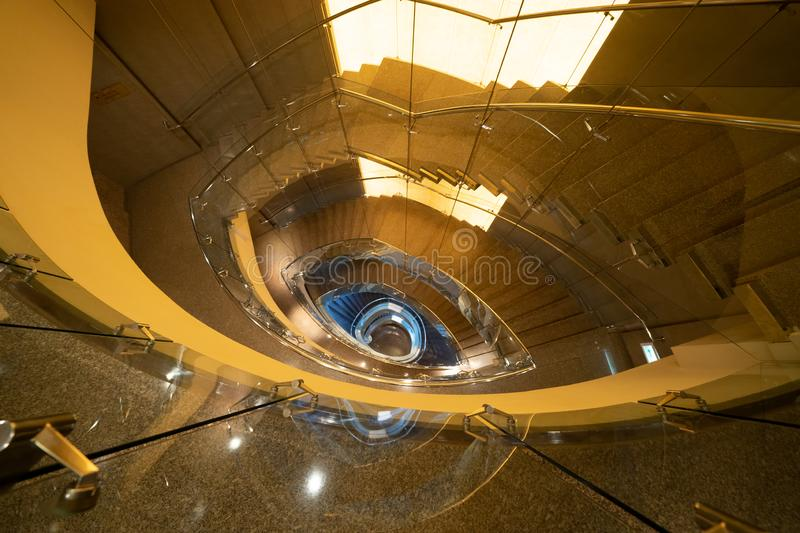 Luxury spiral staircase in lobby hotel with marble floor. Lighting architecture interior design decoration.  stock images