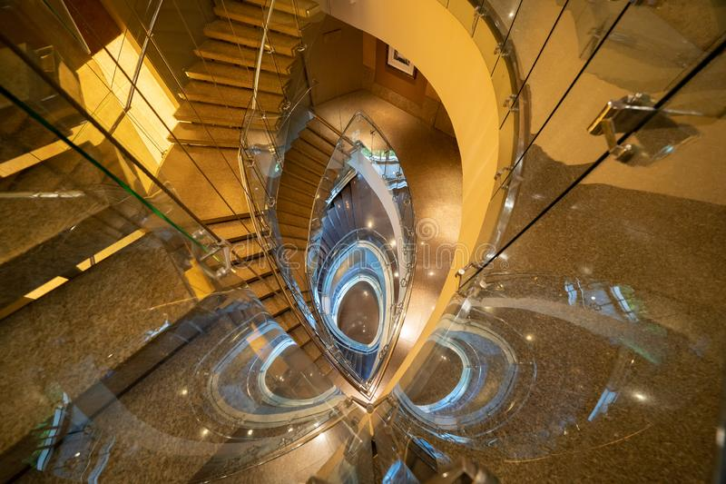 Luxury spiral staircase in lobby hotel with marble floor. Lighting architecture interior design decoration.  royalty free stock photo