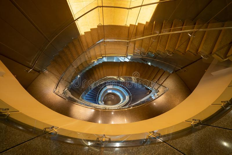 Luxury spiral staircase in lobby hotel with marble floor. Lighting architecture interior design decoration.  stock photos