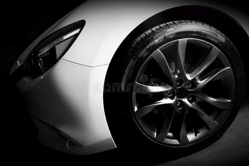 Luxury sports car close up of aluminium rim and headlight. Garage stock photos
