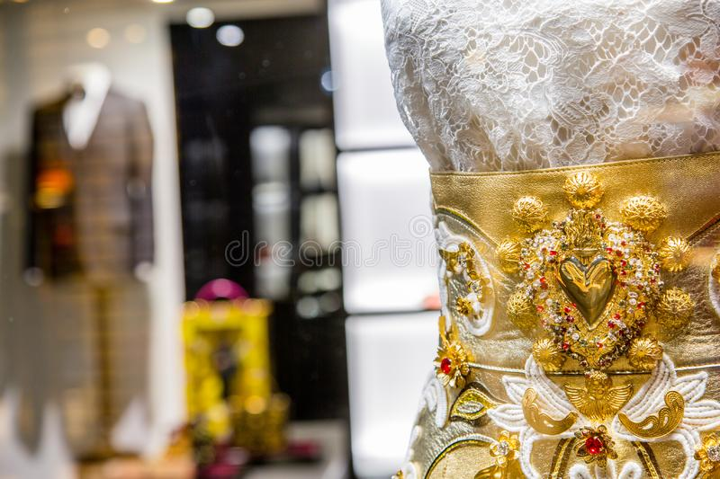 Luxury store with elegant gold dress and suit on background. Italy, Venice - March 21, 2015: Luxury store with elegant gold dress and suit on background royalty free stock image