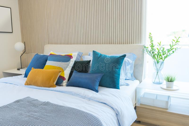 Stylish modern bedroom interior. green, yellow and blue pillow on comfortable bed. Luxury and stylish of modern bedroom interior. green, yellow and blue pillow royalty free stock photos