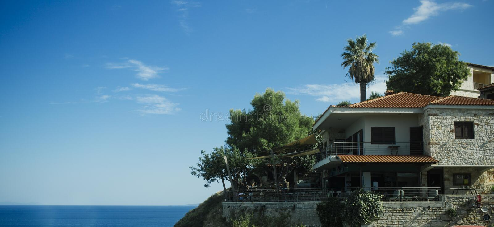 Luxury summer house on hilly sea coast. Building with garden, trees and palm tree. Villa near sea with blue sky on background on. Sunny day, copy space. Luxury stock photography
