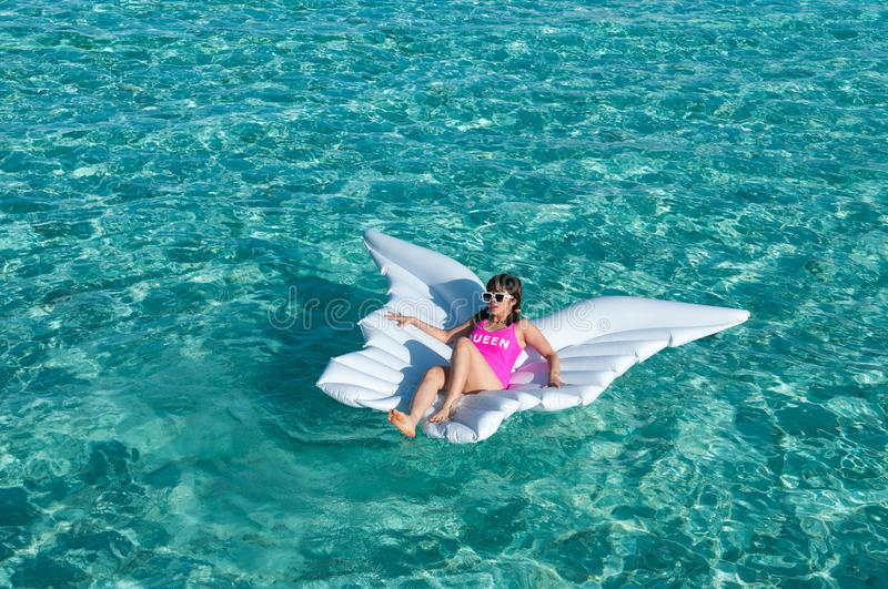 Luxury summer vacation beach woman relaxing lying down on inflatable pool float floating at Maldives sun tanning. Model sleeping o. Luxury summer vacation beach stock image