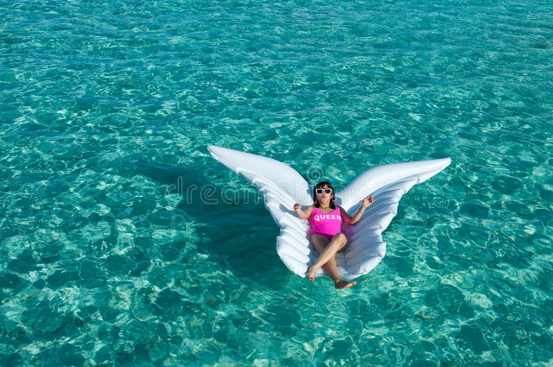Luxury summer vacation beach woman relaxing lying down on inflatable pool float floating at Maldives sun tanning. Model sleeping o. Luxury summer vacation beach stock photo