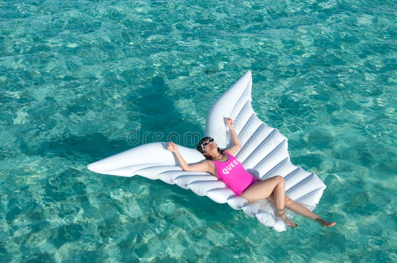 Luxury summer vacation beach woman relaxing lying down on inflatable pool float floating at Maldives sun tanning. Model sleeping o. Luxury summer vacation beach stock photography