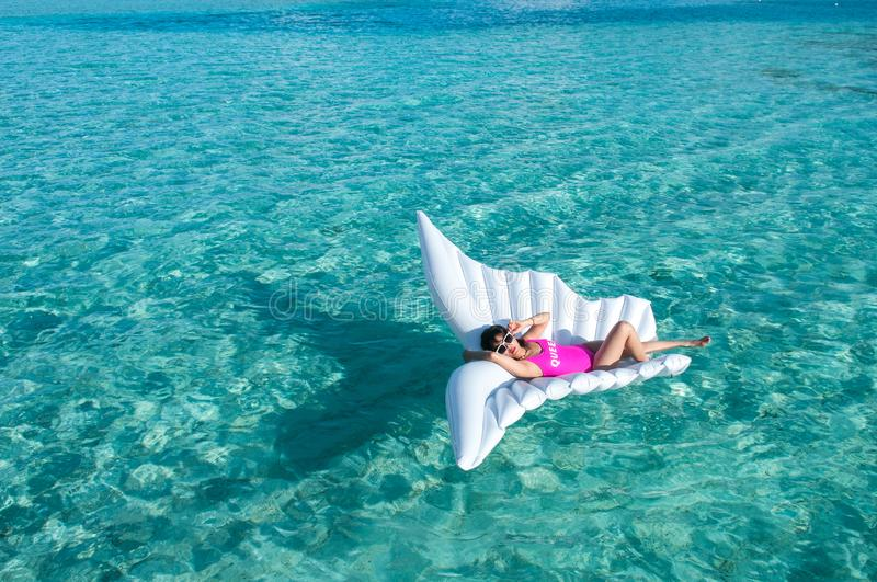 Luxury summer vacation beach woman relaxing lying down on inflatable pool float floating at Maldives sun tanning. Model sleeping o. Luxury summer vacation beach stock photos