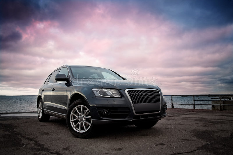 Luxury SUV. Near the sea with dramatic sunset sky royalty free stock photo