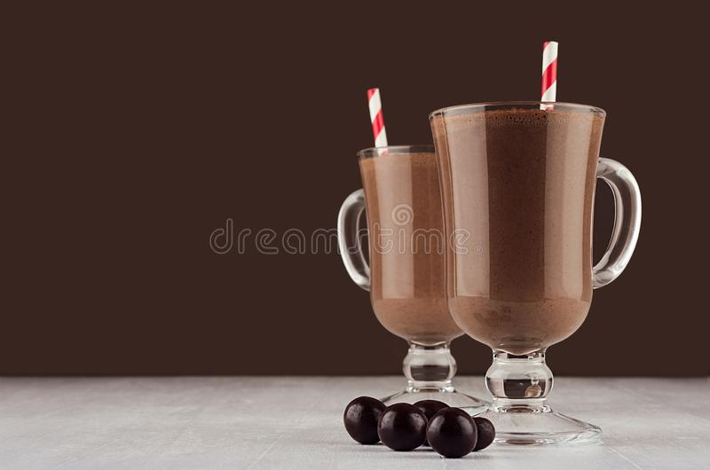 Luxury sweet chocolate dessert in irish coffee glass with round chocolates and red striped straw on dark brown background. Luxury sweet chocolate dessert in stock photo