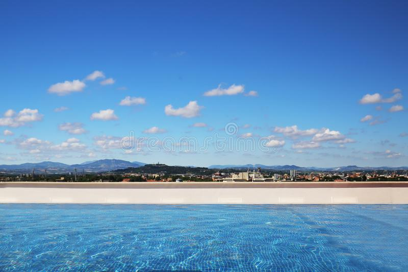 Luxury swimming pool on rooftop. Blue sky with clouds and mountain landscape on background. Panoramic view. Summer travel and vaca royalty free stock photography