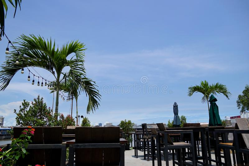 Luxury terrace balcony with dining wooden table and chairs and palm tree. In a restaurant or resort, Outdoor area, Space for text in template stock image