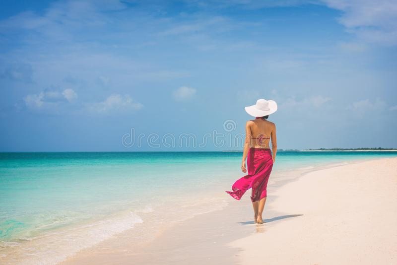 Luxury travel vacation elegant lady walking on beach in pink fashion skirt wrap relaxing on Caribbean holidays in winter stock image