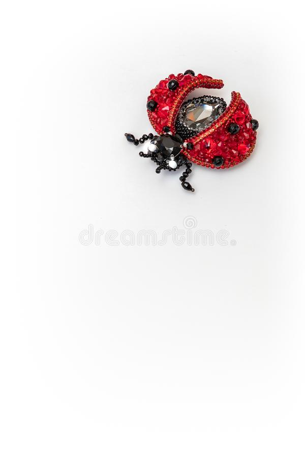Red handmade ladybug brooch on white background stock images