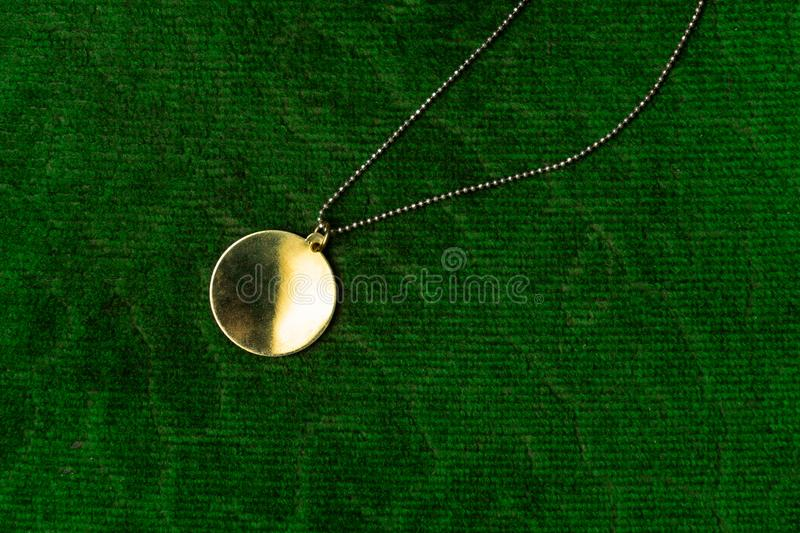 Luxury vintage golden round pendant jewelry with chain necklace accessory for women on green velvet background royalty free stock image
