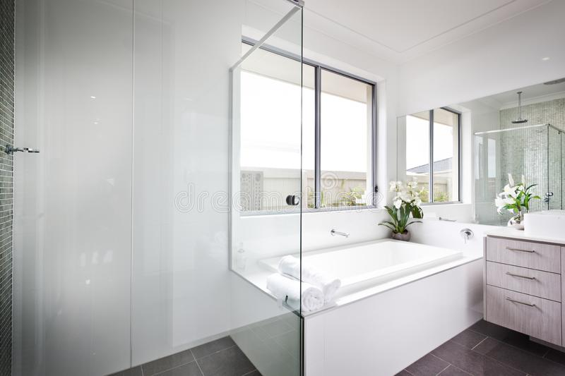 Luxury washroom with white walls and bath tub royalty free stock images