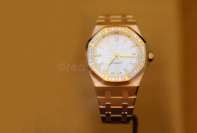 Luxury watches, gold and diamonds. Close up photo of luxury watches: cast golden case inlaid with lots of diamonds, golden arrows and few other masterpiece royalty free stock images
