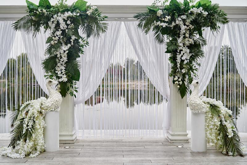 Luxury wedding arch decorated with palm leaves, orchid flowers and floral peacocks outdoors, copy space. Wedding ceremony. Water in park, decoration, beautiful stock photography