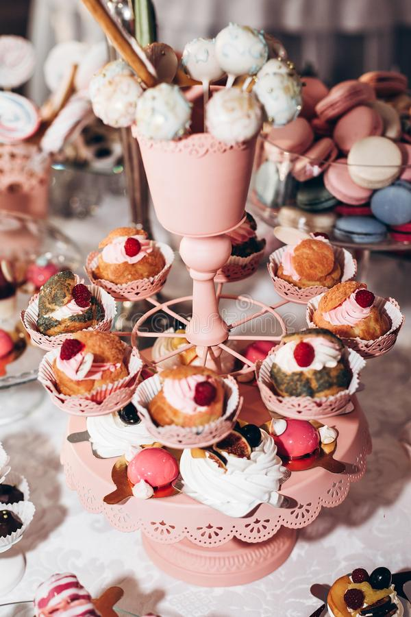 luxury wedding catering, table with modern pops desserts, cupcakes, sweets with fruits. delicious candy bar at expensive wedding royalty free stock image