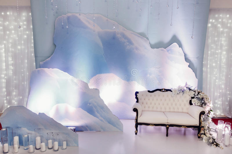 Luxury wedding decor for photo booth zone. stylish chair sofa wi. Th flowers and candles at winter snow instalation. arrangements of decorations at wedding royalty free stock photos