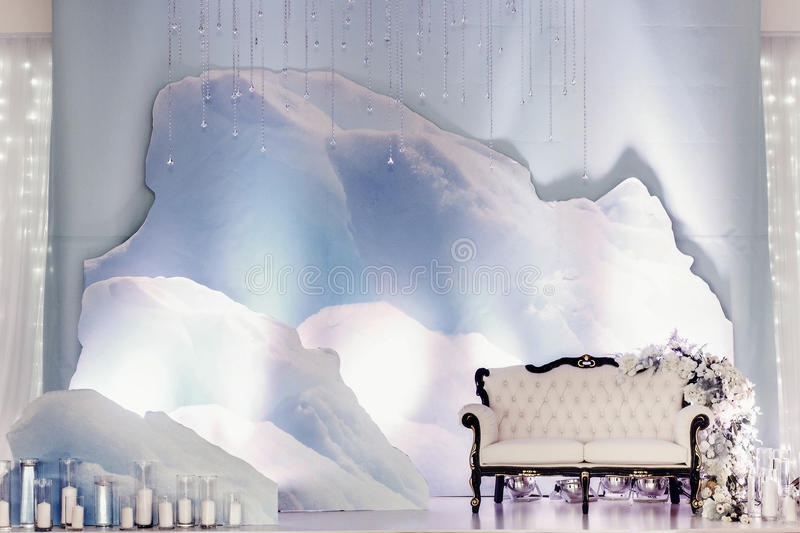 Luxury wedding decor for photo booth zone. stylish chair sofa wi. Th flowers and candles at winter snow instalation. arrangements of decorations at wedding royalty free stock images