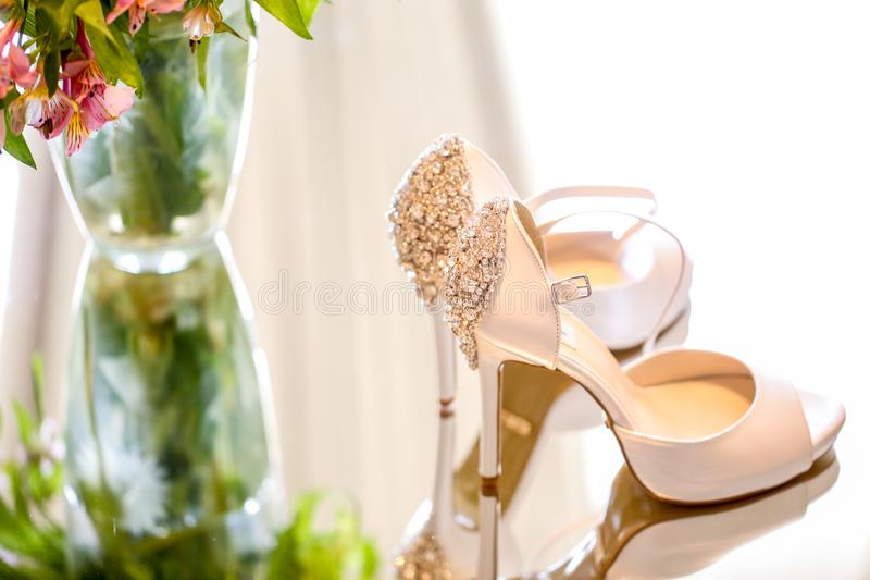 Luxury wedding shoes for bride. Near flowers stock images