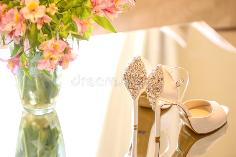 Luxury wedding shoes for bride. Near flowers stock photo