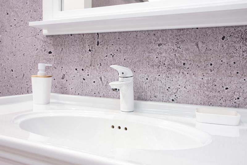 Luxury white faucet mixer on a white sink in a beautiful violet gray bathroom.  stock images
