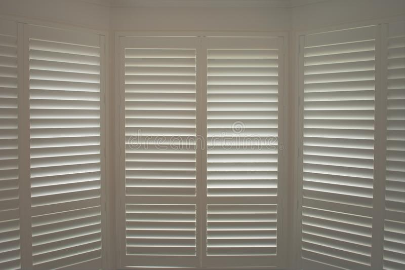 Luxury white indoor plantation shutters, closed shutters. Luxury white indoor plantation shutters closed with day light outside, perfect for every room stock image