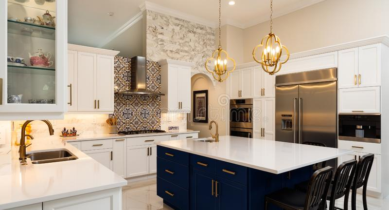 Luxury White Kitchen Home Design. Beautiful luxury estate home kitchen with white cabinets and modern appliances royalty free stock photos