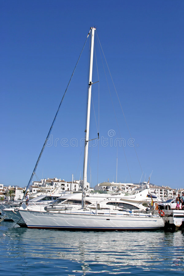 Luxury white yacht with tall mast and reflection in calm port in Spain with sun and blue sky stock photos
