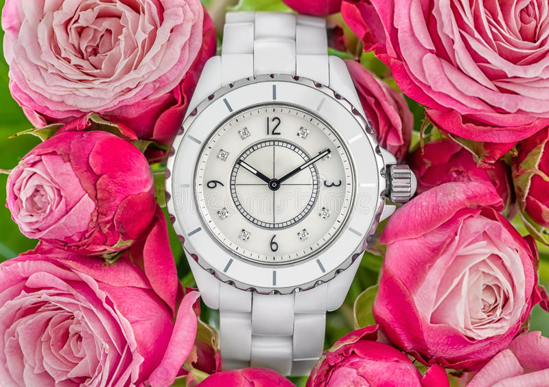 Luxury woman watch. Luxury white woman watch on pink roses back ground stock photo