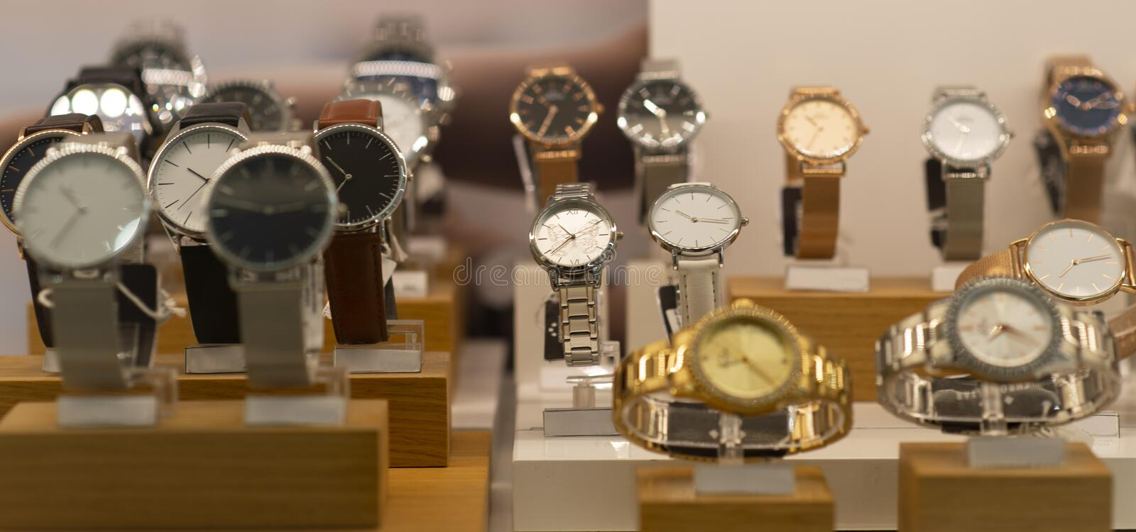 Luxury women`s and men`s watches in the store. Luxury watches in a store stock images