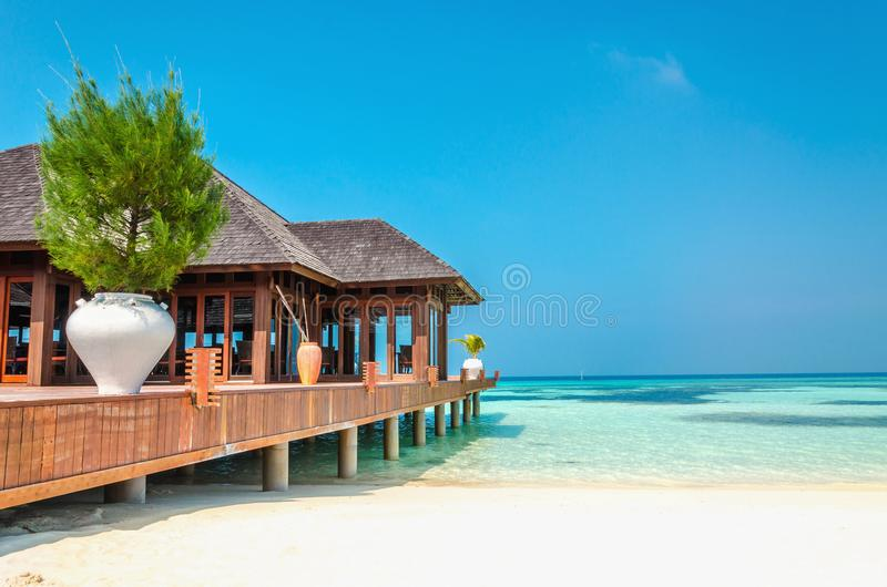 Luxury wooden house on stilts on the background of azure water and beautiful sunny sky royalty free stock image