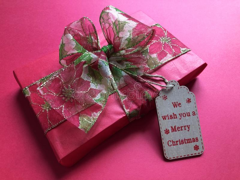 Luxury wrapped Christmas gift on a red background. Beautifully wrapped Christmas present decorated with a poinsettia fabric ribbon tied in a bow on a plain red royalty free stock image