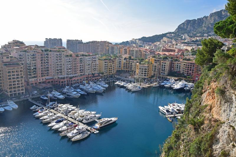 Luxury yacht docking at a harbour in the Principality of Monaco with high rise residential buildings surrounding the coastal line. Monaco is a sovereign city royalty free stock photo