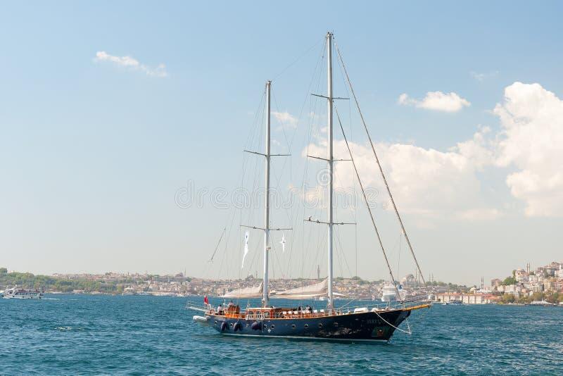 Luxury yacht and Istanbul shoreline of Bosphorus strait. Private luxury yacht sailing on Bosporus strait, Istanbul, Turkey stock photography
