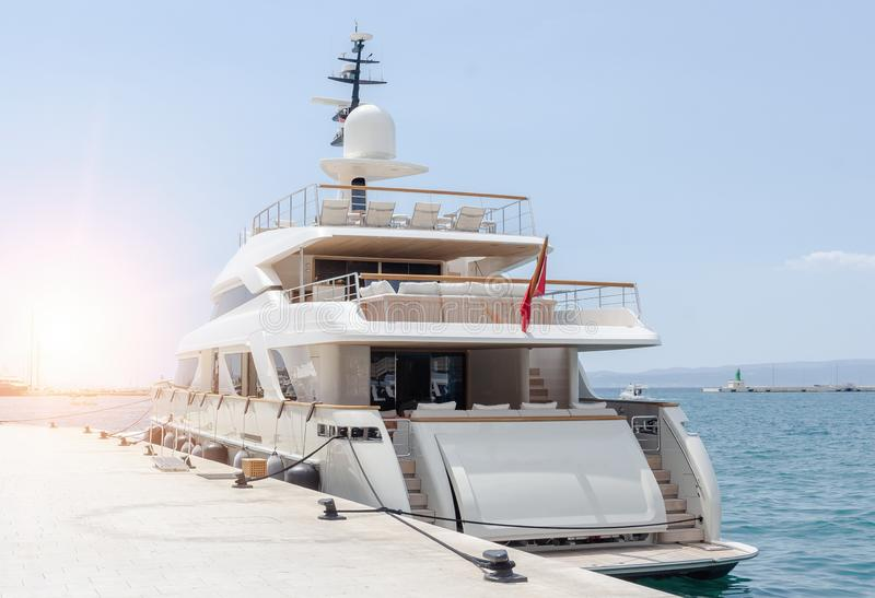 Luxury yacht parked at dock. Luxury white yacht parked at sea dock royalty free stock photos