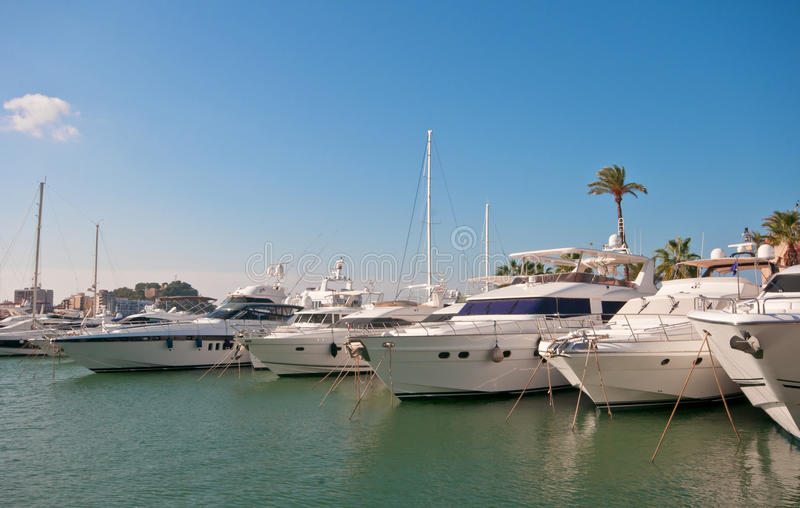 Luxury yachts moored in marina. Luxury yachts lined up in Denia marina, Spain. Orange lifebelt in the foreground. Sunny with blue sky and light cloud stock photo