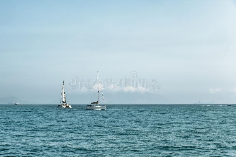 Luxury yachts in open sea at beautiful sunny day. Active lifestyle for active people. Tropical vacation. Weekend getaway. royalty free stock photography