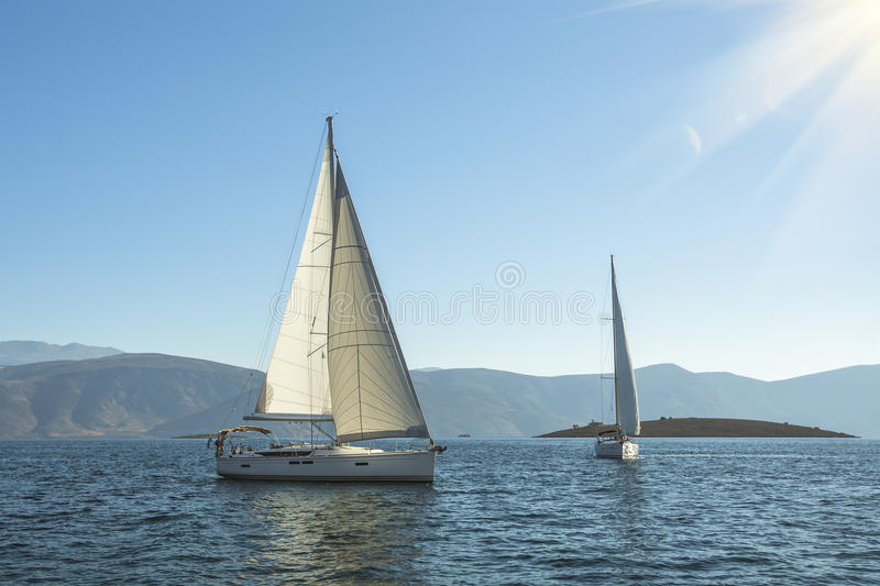 Luxury yachts in the sea near the Greek Islands in the rays of the rising sun. Sailing. Luxury yachts in the sea near the Greek Islands in the rays of the stock image