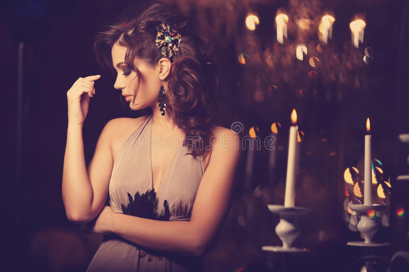 Luxury young woman in expensive interior. Girl with flawless makeup and evening volume hairstyle. Luxury young woman in expensive interior. Young girl with royalty free stock image