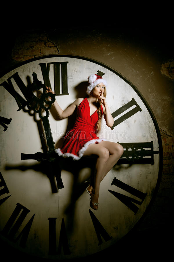 Luxury young woman in Santa costume on the big dial. Girl and cl. Trendy young woman in Santa costume on the big dial. Girl and clock in Christmas. New Year royalty free stock photos
