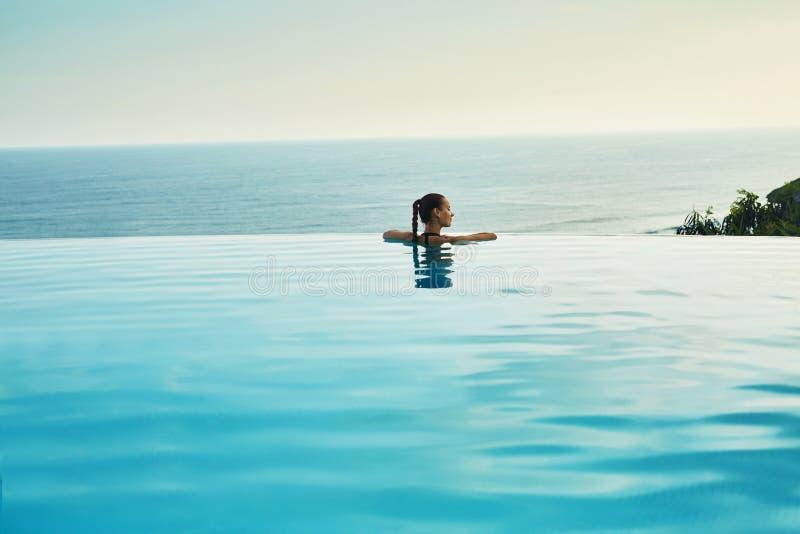 Luxus-Resort Frau, die im Pool sich entspannt Sommer-Reise-Ferien lizenzfreie stockfotografie