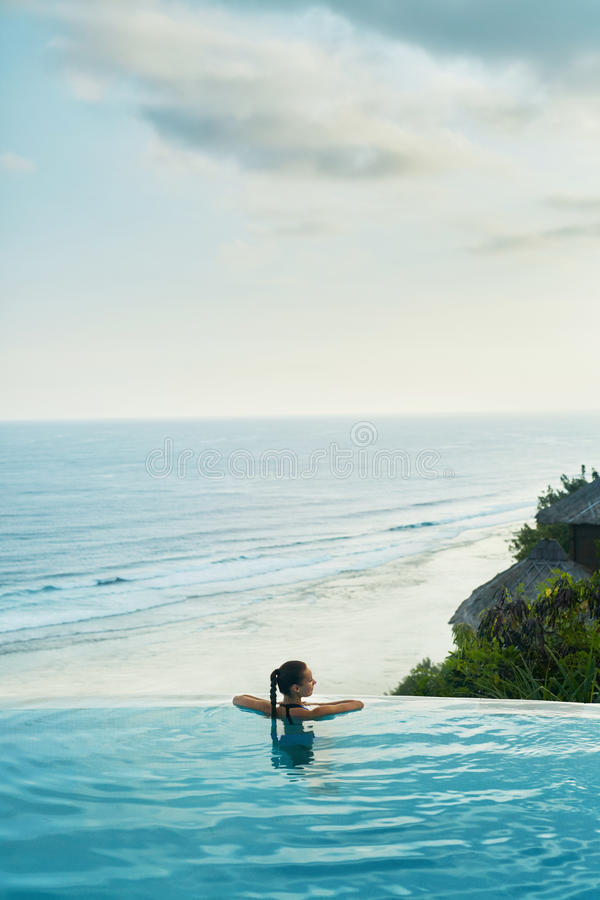 Luxus-Resort Frau, die im Pool sich entspannt Sommer-Reise-Ferien lizenzfreie stockfotos