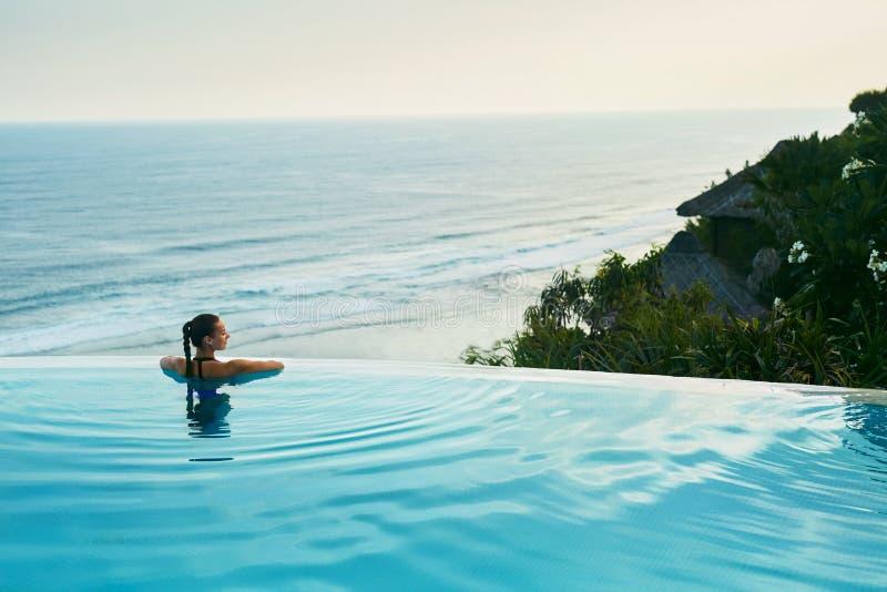 Luxus-Resort Frau, die im Pool sich entspannt Sommer-Reise-Ferien stockbild