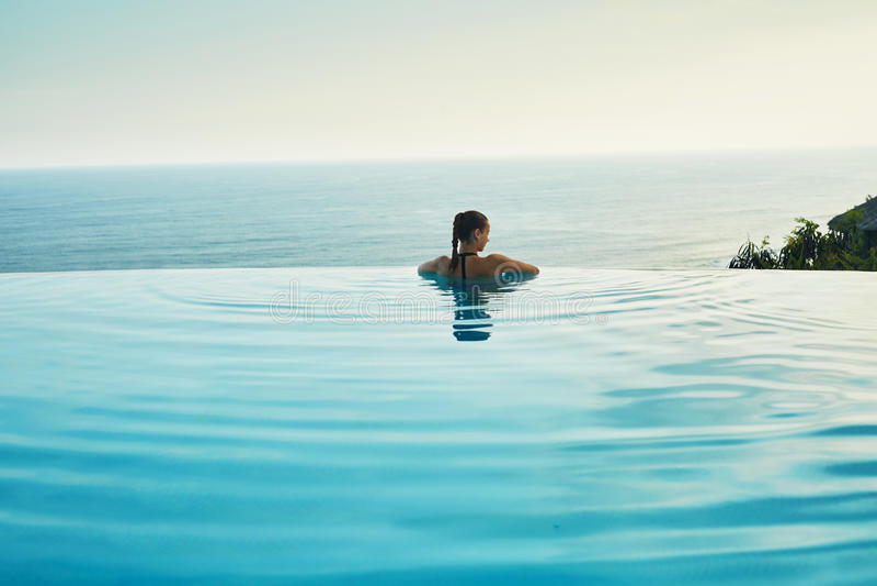 Luxus-Resort Frau, die im Pool sich entspannt Sommer-Reise-Ferien stockfotos