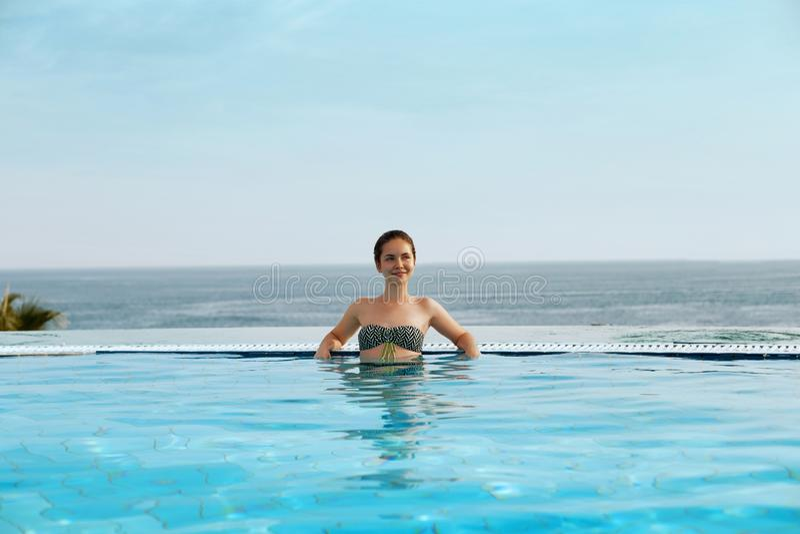 Luxus-Resort Frau, die im Unendlichkeits-Swimmingpool-Wasser sich entspannt Sch?nes gl?ckliches gesundes weibliches vorbildliches lizenzfreie stockfotos