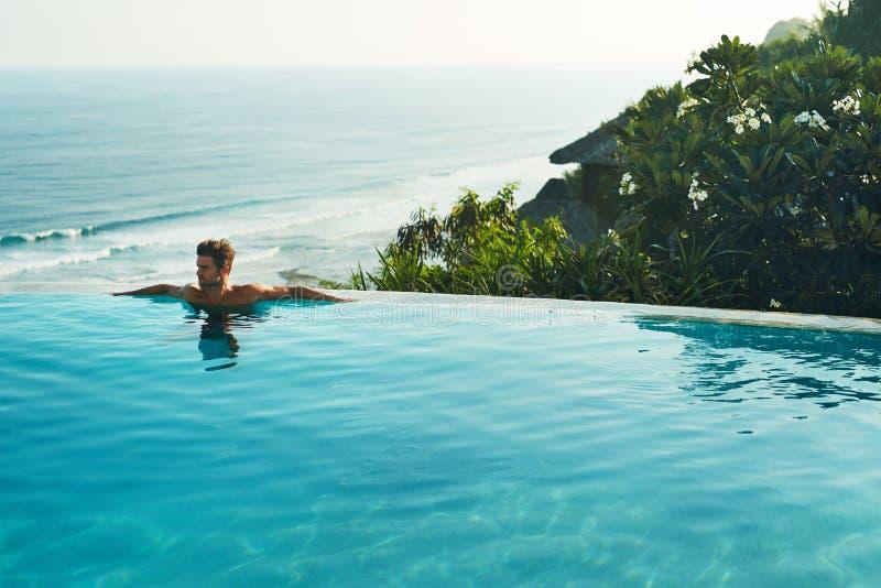 Luxus-Resort Mann, der im Schwimmen-Pool sich entspannt Sommer-Reise-Ferien lizenzfreie stockfotos