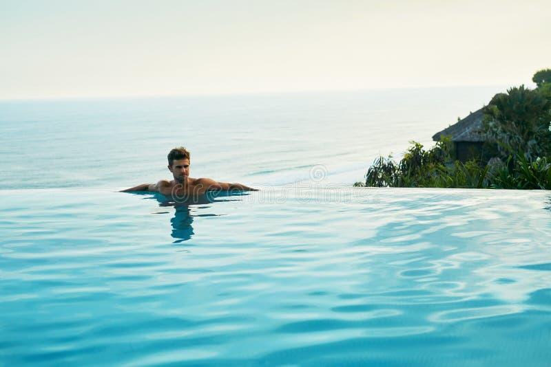 Luxus-Resort Mann, der im Schwimmen-Pool sich entspannt Sommer-Reise-Ferien stockfotos