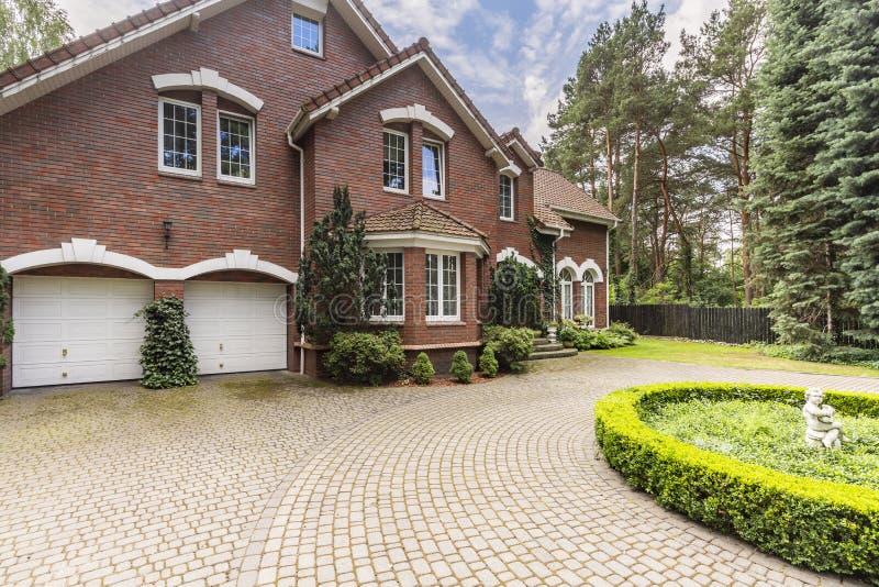 Luxus- und großes Haus in der englischen Art mit Garten und Fahrstraße lizenzfreies stockfoto